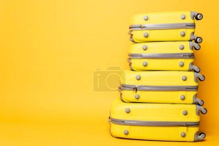 pila de bolsas de viaje sobre fondo amarillo