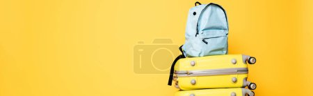 Photo for Blue backpack on travel bags isolated on yellow, panoramic shot - Royalty Free Image