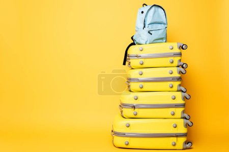 Photo for Blue backpack on travel bags isolated on yellow - Royalty Free Image