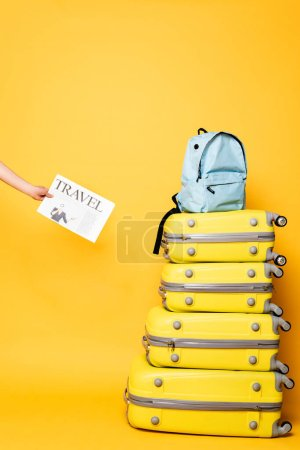 Photo for Cropped view of woman holding travel newspaper near blue backpack on travel bags on yellow - Royalty Free Image