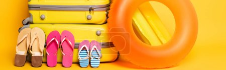 Photo for Travel bags with family flip flops and pool floats on yellow, panoramic shot - Royalty Free Image