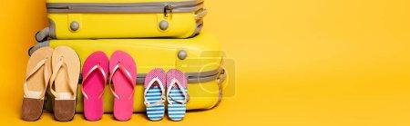 Photo pour Sacs de voyage avec des tongs familiales isolées sur jaune, panoramique - image libre de droit