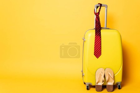 Photo for Yellow travel bag with red tie and flip flops isolated on yellow - Royalty Free Image