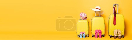Photo for Family travel bags with beach summer accessories isolated on yellow, panoramic shot - Royalty Free Image