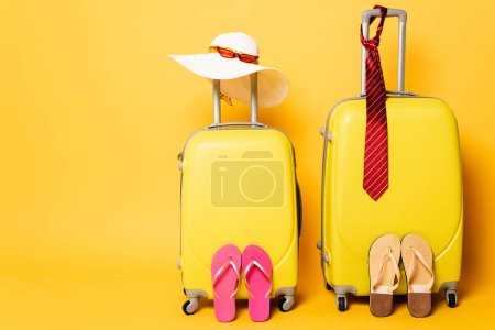 Photo for Travel bags with male and female accessories isolated on yellow - Royalty Free Image