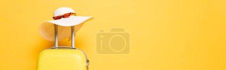Photo pour Sac de voyage jaune avec chapeau de soleil et lunettes de soleil isolés sur jaune, panoramique - image libre de droit