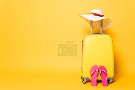 Photo for Yellow travel bag with flip flops, sun hat and sunglasses isolated on yellow - Royalty Free Image