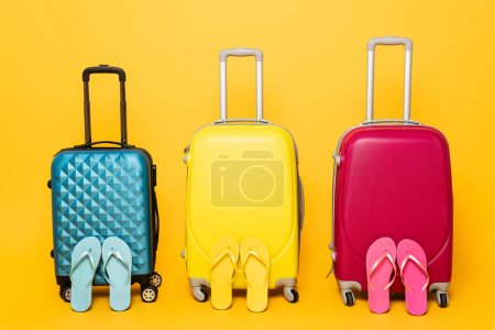 Photo for Yellow, pink and blue travel bags with flip flops isolated on yellow - Royalty Free Image