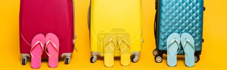 Photo for Yellow, pink and blue travel bags with flip flops isolated on yellow, panoramic shot - Royalty Free Image