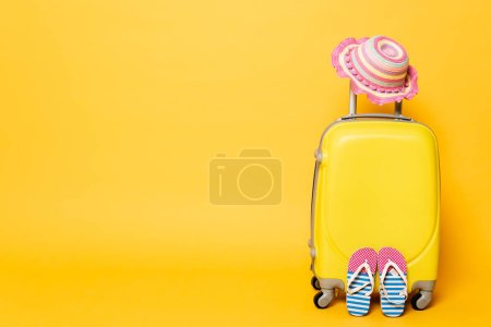 Photo for Yellow travel bag with child sun hat and flip flops isolated on yellow - Royalty Free Image