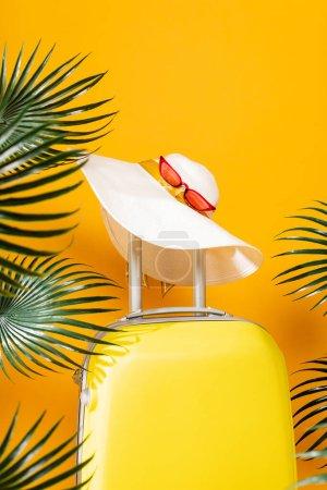 Photo pour Sac de voyage jaune avec chapeau et lunettes de soleil près des feuilles de palmier vert sur fond jaune - image libre de droit