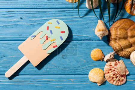 Photo for Top view of paper ice cream with sprinkles near seashells and palm leaf on wooden blue background - Royalty Free Image