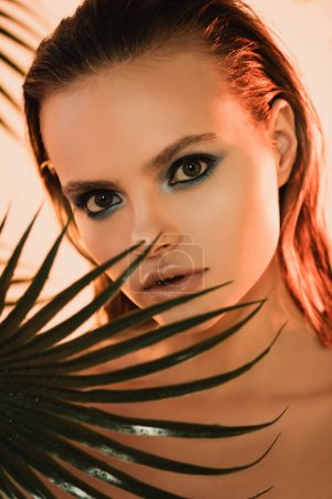 Photo for Selective focus of beautiful woman with blue eye shadow looking at camera near palm leaf - Royalty Free Image