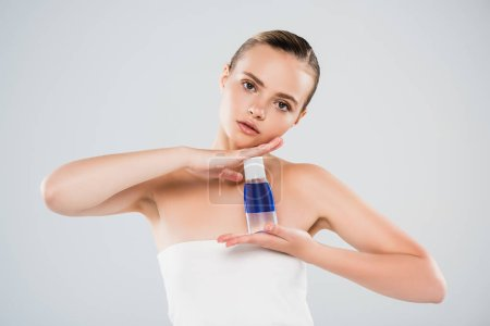 pretty woman holding bottle with toner isolated on grey