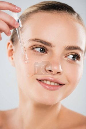 close up of happy woman holding pipette and applying serum isolated on grey