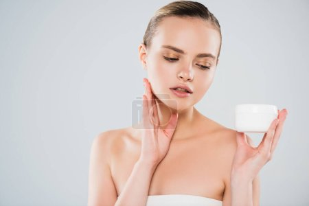 Photo for Pretty woman looking at container with face cream isolated on grey - Royalty Free Image