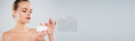 Photo for Panoramic shot of pretty woman holding container with face cream isolated on grey - Royalty Free Image