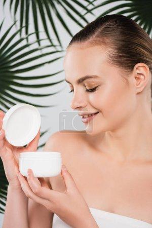 Photo pour Femme heureuse regardant le récipient avec crème visage près des feuilles de palmier sur blanc - image libre de droit