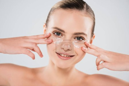 Photo for Smiling and naked woman touching eye patches isolated on grey - Royalty Free Image