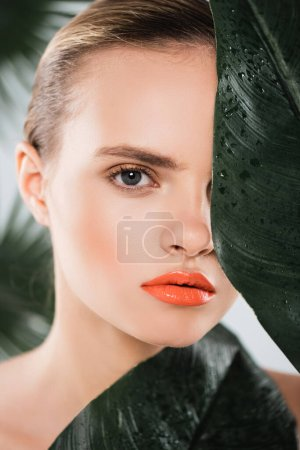 Photo for Beautiful girl with makeup looking at camera near green and wet leaf on white - Royalty Free Image