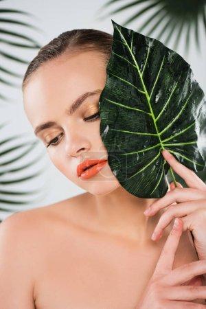 Photo pour Belle fille avec maquillage tenant la feuille verte et humide sur blanc - image libre de droit