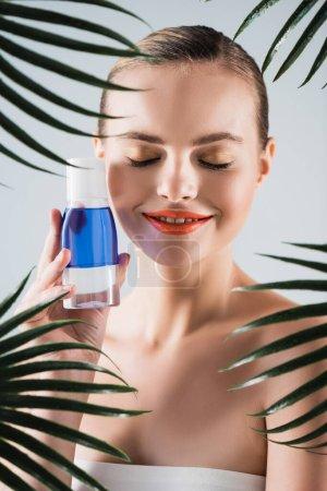 Foto de Mujer feliz con maquillaje celebración botella con tóner cerca de hojas de palma en blanco - Imagen libre de derechos