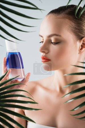 Photo for Attractive woman with makeup looking at bottle with toner near palm leaves on white - Royalty Free Image