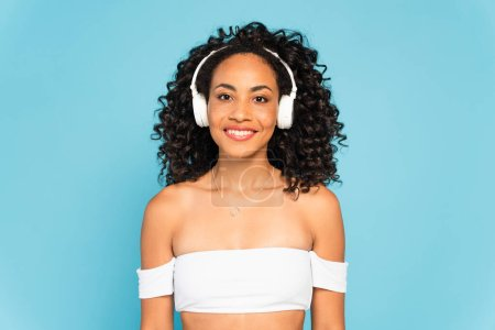 Photo for Happy african american girl listening music in wireless headphones isolated on blue - Royalty Free Image