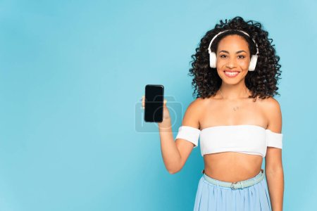 happy african american woman listening music in wireless headphones and holding smartphone with blank screen isolated on blue