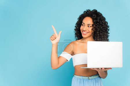 Photo for Happy african american woman holding laptop and pointing with finger on blue - Royalty Free Image
