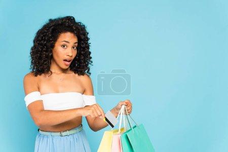Photo pour Choqué afro-américaine fille tenant carte de crédit et sacs à provisions sur bleu - image libre de droit