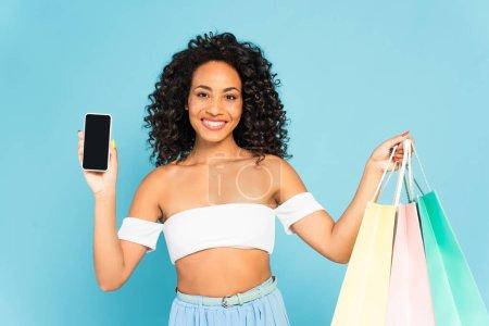 Photo pour Femme afro-américaine souriante tenant des sacs à provisions et smartphone avec écran blanc isolé sur bleu - image libre de droit