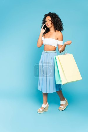 Photo for Positive african american girl holding shopping bags and talking on smartphone on blue - Royalty Free Image