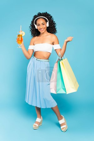 cheerful african american girl holding shopping bags and cocktail while listening music in headphones on blue