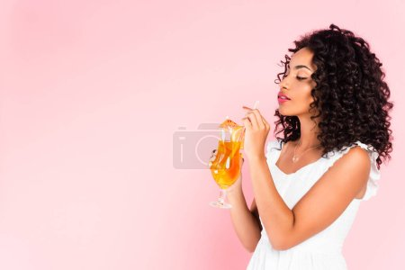 african american girl looking at glass with cocktail on pink