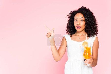 Photo pour Surpris afro-américaine fille pointant du doigt et tenant cocktail sur rose - image libre de droit
