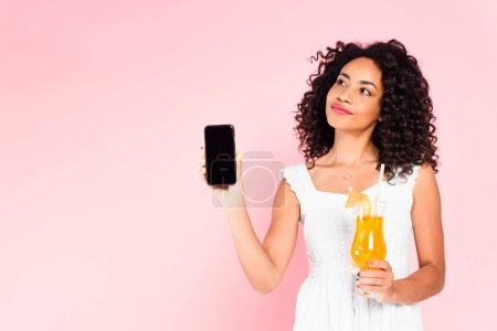 curly african american girl holding smartphone with blank screen and cocktail on pink