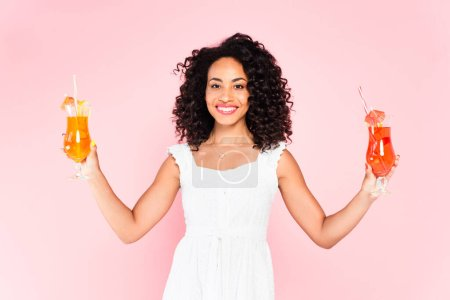 Photo for Happy african american girl holding cocktails on pink - Royalty Free Image