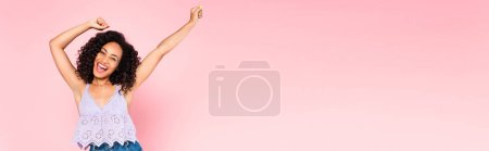 horizontal image of excited african american woman with hands above head on pink