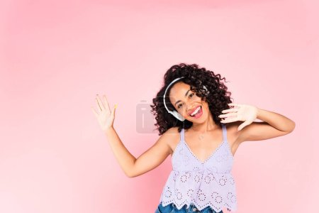 excited african american girl in wireless headphones listening music isolated on pink