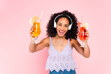 cheerful african american girl in wireless headphones listening music and holding cocktails isolated on pink