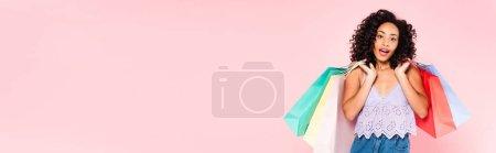 Photo pour Image horizontale de fille afro-américaine surprise tenant des sacs à provisions isolés sur rose - image libre de droit