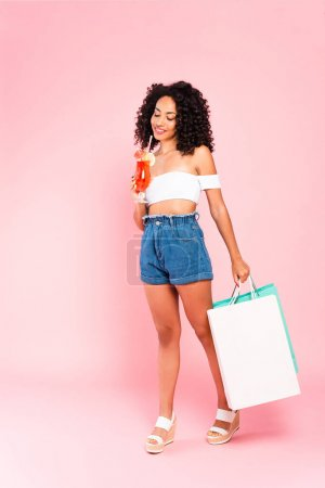 Photo for Cheerful african american woman holding cocktail and shopping bags on pink - Royalty Free Image