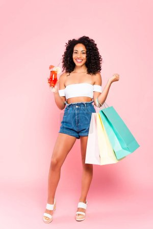 Photo for Happy african american woman holding cocktail and shopping bags on pink - Royalty Free Image