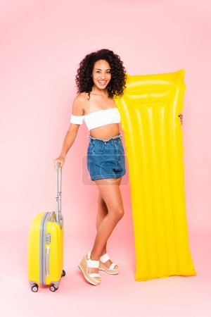 smiling african american girl holding inflatable mattress and standing near luggage on pink