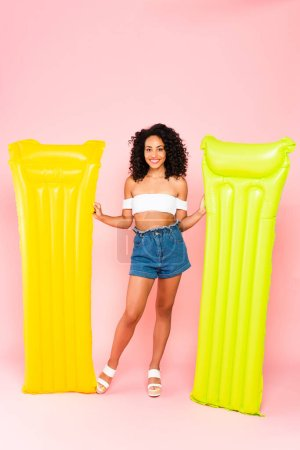 Photo for Cheerful african american girl standing near inflatable mattresses on pink - Royalty Free Image