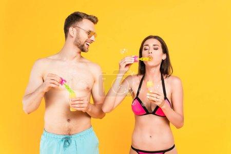 hombre feliz y sin camisa en gafas de sol mirando a la chica en traje de baño soplando burbujas de jabón aislado en amarillo