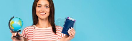 horizontal image of happy girl holding passport and globe isolated on blue