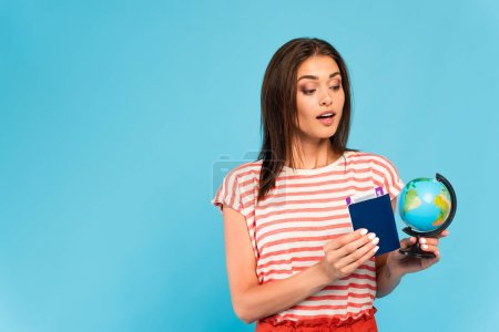 Photo for Surprised girl holding passport and looking at globe isolated on blue - Royalty Free Image