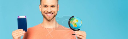 horizontal concept of happy man holding passport and globe isolated on blue
